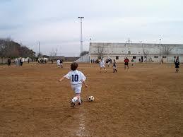 superficie de tierra campo de fútbol, niños jugando en cancha grande